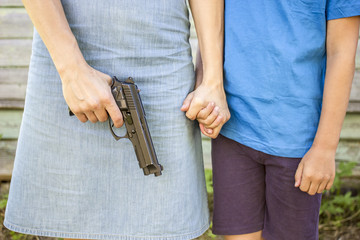 Woman holds the gun in one hand, nearby there is a the boy whom she strongly holding his hand, outdoors