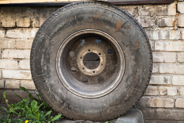 Old used car wheel stands near wall