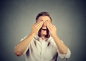 Surprised man covering his eyes with hands