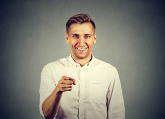 Portrait of a young man pointing his finger at you