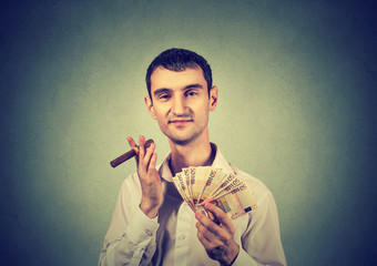 Happy young confident man with euro banknotes money and cigar
