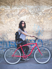 Young mixed race curly black hair woman holding a bicycle in a street of the city, with headphones around her neck, looking in camera, serious- youth, sportive, carefree concept