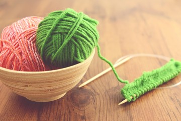 knitting with green wool on wooden table