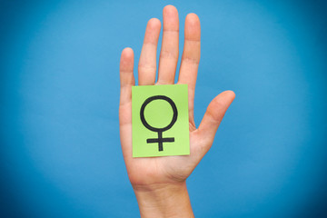 Green paper note with female gender symbol