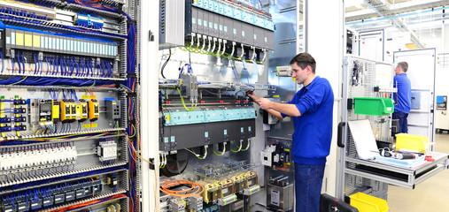Facharbeiter montiert elektronische Schaltanlage in einer Fabrik // workers mounted switchgear in an industrial plant