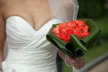 Bride holds red wedding bouquet behind her seductive chest