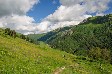Girl with a big backpack is traveling in the Caucasus mountains, Georgia.