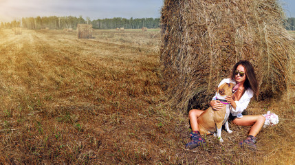 Woman Sitting With Dog at Straw Bale In Harvested Field