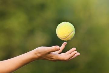 hand tossing tennis ball