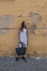 Woman and old wall with handbag