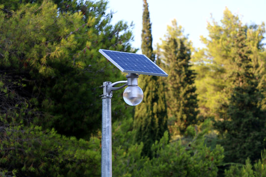 Solar street light, trees in the background. Sustainable town concept.