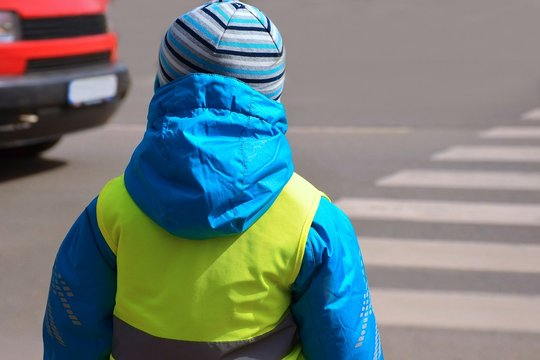 Little boy is going to cross zebra crossing where red car is approaching. Child is wearing yellow reflective vest and jacket with reflective strips because of safety.
