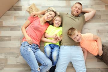 Happy family lying on wooden floor