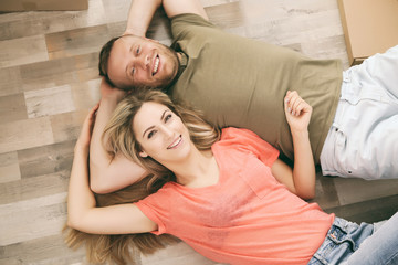 Beautiful couple lying on wooden floor