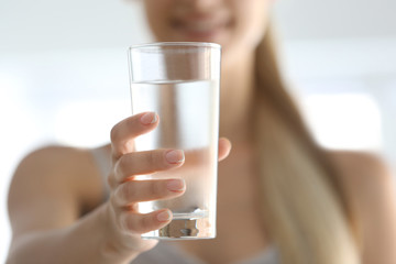 Girl drinking water on light background