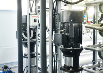 Large industrial water treatment and boiler room. Water pumps
