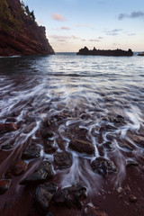 Red sand at waters edge, Kauai, Hawaii, United States of America