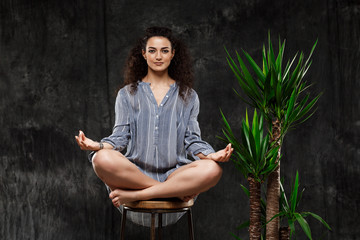 Beautiful brunette girl meditating in tropical plants over grey background.