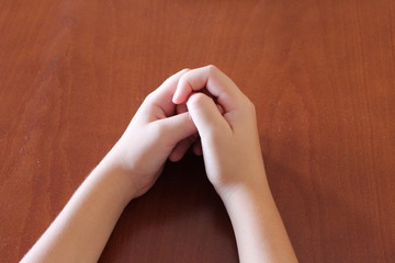 hands on the table,bonded fingers,wooden furniture,two arms,body parts,children's hands,calm hands are placed on the table,pending,emotionless,hand posture,