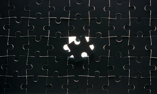 Assembled black puzzle with one wrong-placed element
