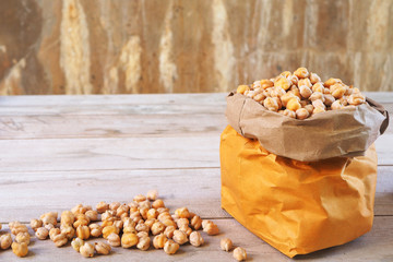 Dried chickpeas in a brown bag and a pile on wooden table.