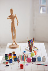 paints brushes for drawing and wooden figure