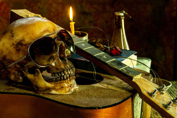 Still life with human skull bespectacled on guitar background