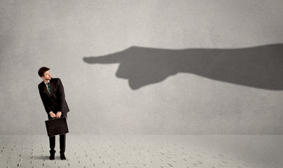 Business person looking at huge shadow hand pointing at him conc