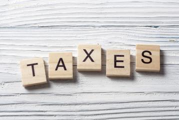 Taxes word written on wood abc block