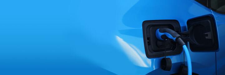 Elektroauto beim Aufladen an der Ladestation - Ladestecker - Alternative Energie