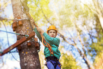 kid ready to zip line flight in adventure park. ziplining. brave child is ready to jump from a height. empty space for your text