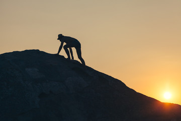 Man climbing up the hill to reach the peak in sunset