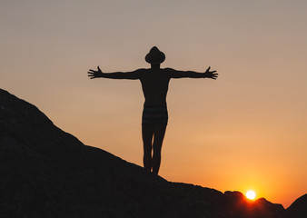 Silhouette of man raising hands in the sunset on the cliff