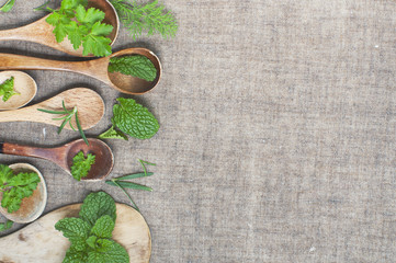 fresh herbs and wooden spoons on a linen background