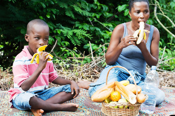 young woman and her son eat bananas during a relaxing out