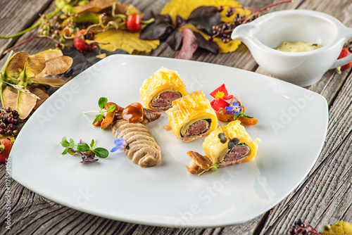 exclusive puff pastry appetizer with meat pie decorated with mushrooms and herbs on white plate with & exclusive puff pastry appetizer with meat pie decorated with ...