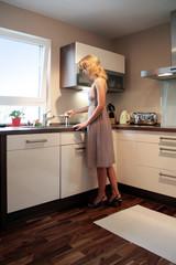 Frau steht in Küche am Waschbecken