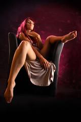 Frau sitzt provokant breitbeinig auf Sessel