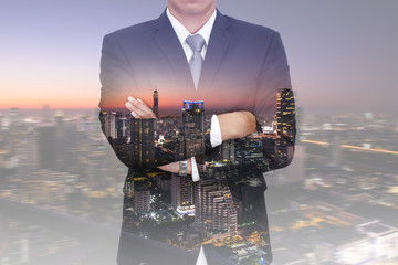 Double exposure of business man arms crossed, skyline and night cityscape as vision of leader, future concept.