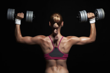athletic bodybuilder young woman with dumbbells.girl with muscles in gym