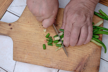 Cut with a knife raw green beans on a wooden board,