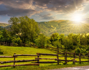 wooden fence on hillside at sunset