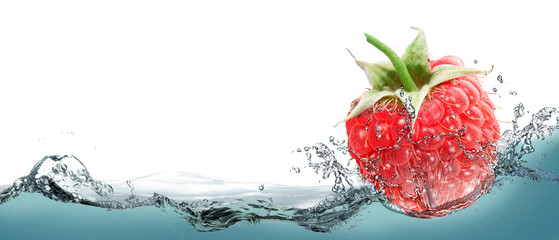Raspberries in a spray of water.