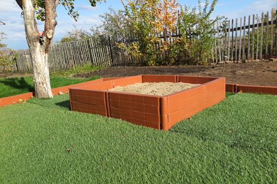 Modern plastic sanbox on the artificial lawn in the sunny autumn garden