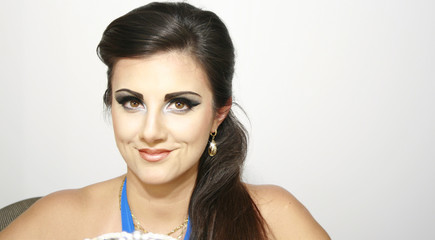 Beautiful smiley girl  with  blue intense makeup and earings, with long dark hair