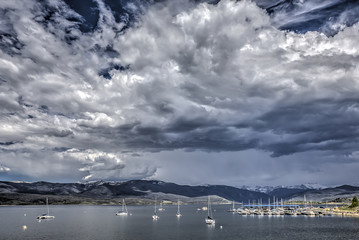 Sail boats at anchor on Grand Lake Colorado with a building storm in the sky.