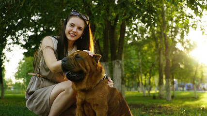young woman walking in the park with a Shar-Pei