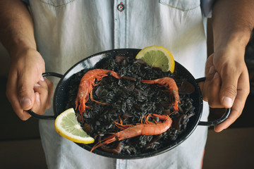 Man Holding Traditional Spanish Black Rice with Seafood