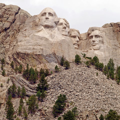 Sculpted images under a cloudy sky of Presidents George Washington, Thomas Jefferson, Theodore Roosevelt, and Abraham Lincoln at Mt. Rushmore National Memorial, Keystone, South Dakota, U.S.A.