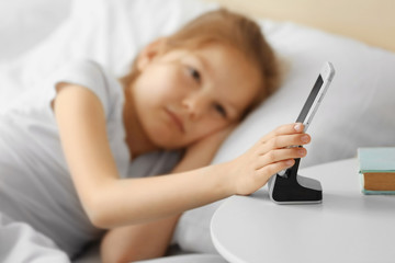 Cute girl with alarm mobile clock in white bed
